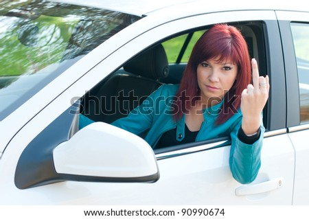 Negative female driver sitting behind the wheel and showing her middle finger - stock photo