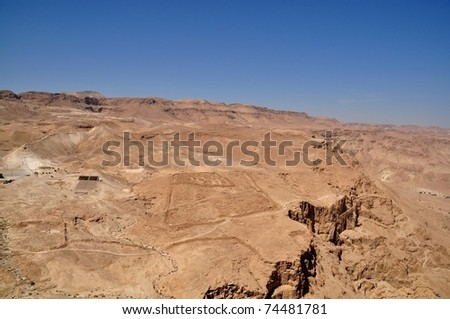 Negev desert view from Masada. Barren and rocky. Roman fortification ruins at the left. - stock photo