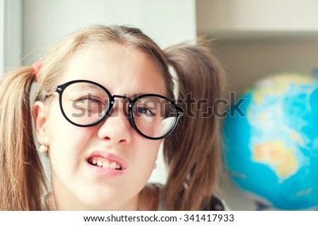 Neglecting the school. Nerdy funny girl with ponytails in eyeglasses. Indoors vibrant closeup horizontal image. - stock photo