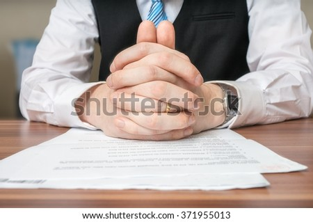 Negotiation with lawyer who is sitting behind desk and has clasped hands on document. - stock photo