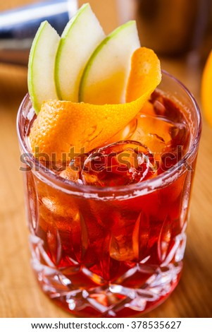 Negroni cocktail decorated with orange swirl and apple slices - stock photo