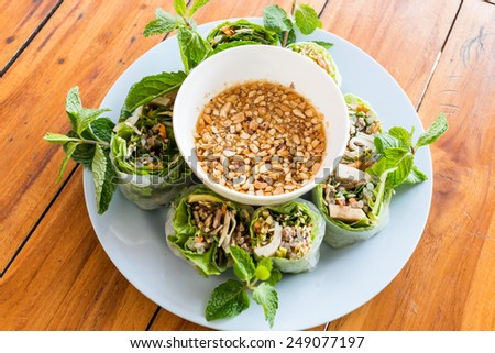 Nem Cuon - Vietnam food,Vietnamese fresh summer rolls filled with prawns, pork, herbs, rice vermicelli and vegetables. Served with hoisin and peanut sauce dip and nuoc mam cham - stock photo