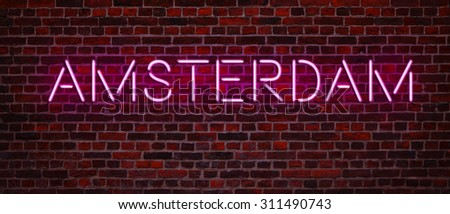 Neon Letters - Word Amsterdam on the old red brick wall  - stock photo
