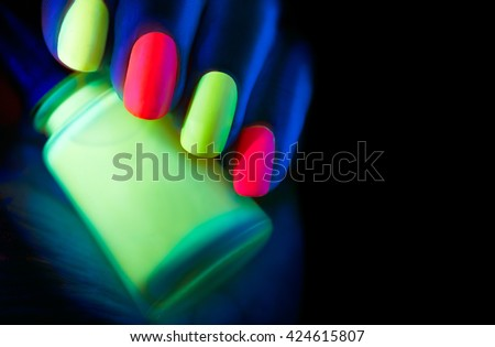 Neon Nails. Fashion model woman nails in neon light, beautiful nail art with fluorescent nail polish, Art design of female colorful disco nailart in UV, Isolated on black background - stock photo