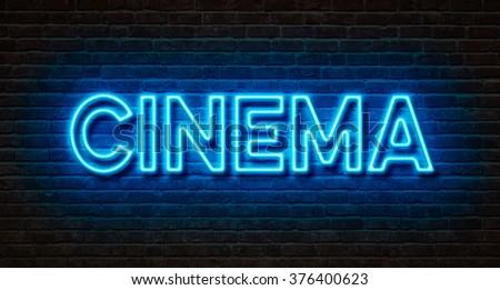 Neon sign on a brick wall - Cinema - stock photo