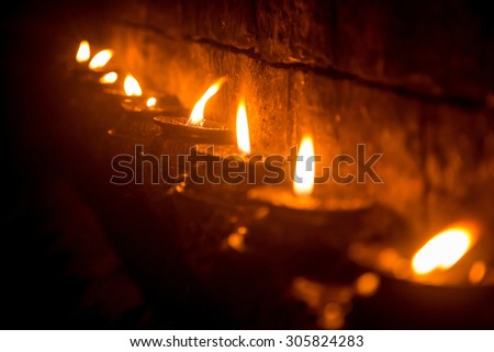 Nepalese candles lighting a temple wall - stock photo