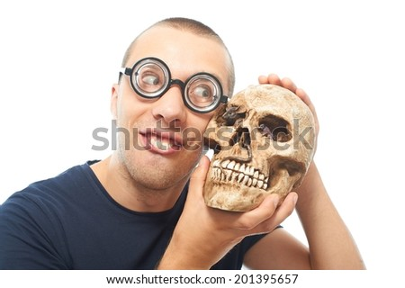 Nerd in eyeglasses and his only friend skull - stock photo