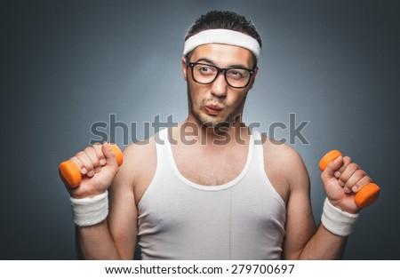 Nerd man exercising and doing sport training. Humorous athletic man using small dumbbells for bodybuilding. Dark gray background. Studio shot - stock photo