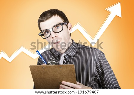 Nerd stock market analyst writing up a financial report on rising interest in the commodities market - stock photo