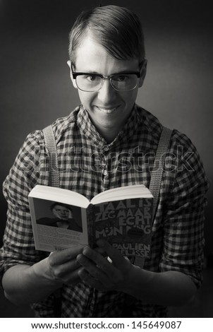 nerd with book and glasses - stock photo