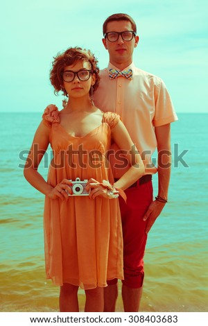 Nerds' honeymoon concept. Portrait of couple of young happy married hipsters in trendy vintage clothes standing together on the beach and making selfie. Sunny summer day. Outdoor shot - stock photo
