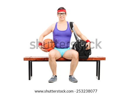 Nerdy athlete holding a basketball seated on a bench isolated on white background - stock photo