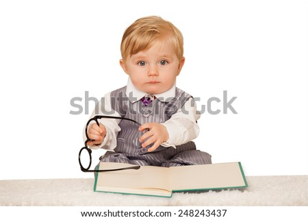 Nerdy baby boy reading a book - stock photo