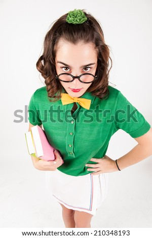 nerdy girl holding books looking at camera. - stock photo