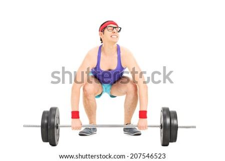 Nerdy guy struggling to lift a barbell isolated on white background - stock photo