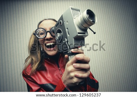 Nerdy woman using old fashioned cine camera - stock photo