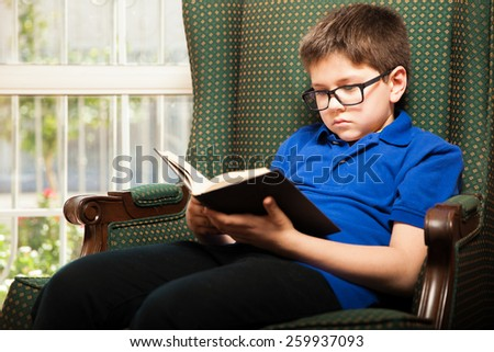 Nerdy young kid with glasses reading his favorite book while relaxing at home - stock photo