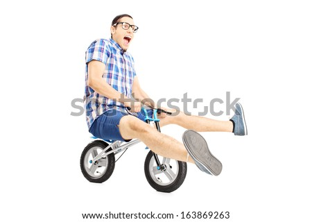 Nerdy young male riding a small bicycle isolated on white background - stock photo