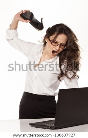 nervous and angry business woman destroys her laptop with high heels - stock photo