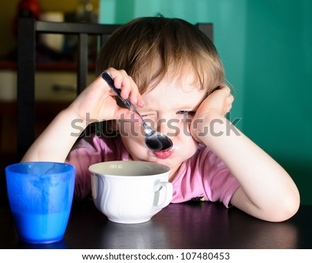 Nervous little boy eating and drinking milk - stock photo