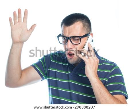 Nervous man on phone. Irritated young guy talking on mobilephone, isolated on white background, studio shot. - stock photo