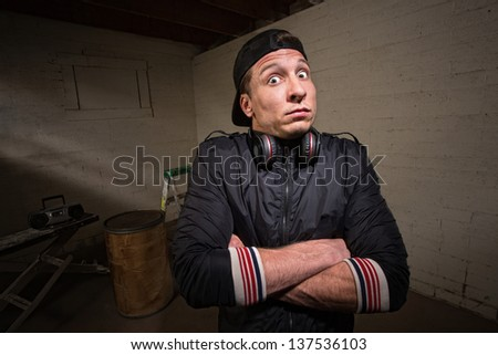Nervous man with headphones and folded arms - stock photo