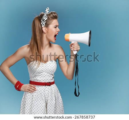 Nervous pin-up girl screaming with megaphone, mouthpiece, speaking trumpet. Film-making or film production concept / photo set of young American pin-up model on blue background - stock photo
