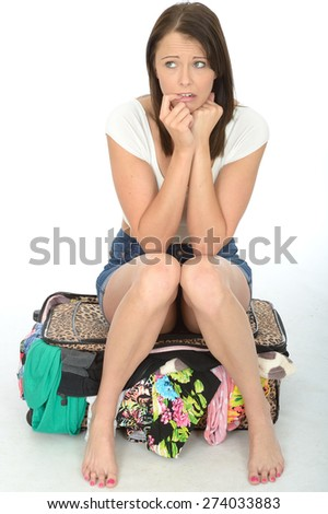 Nervous Scared Attractive Young Woman Sitting on a Suitcase Looking Worried - stock photo
