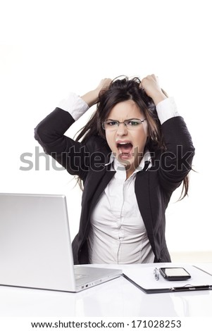 nervous young business woman at the desk with a laptop chip her hair and screaming - stock photo