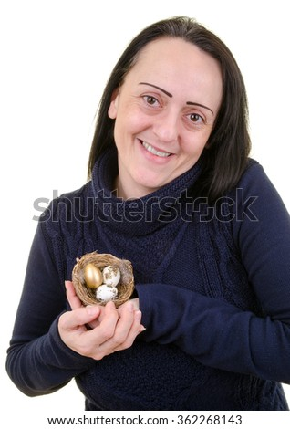 Nest egg. Pension or retirement fund. Smiling, happy woman caring for a nest full of eggs including a golden egg. Portrait on white background - stock photo