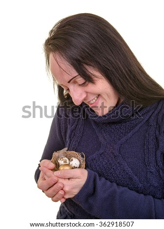 Nest egg. Pension or retirement fund. Smiling woman caring for a nest full of eggs including a golden egg. Portrait on white background - stock photo