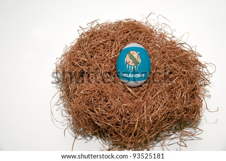 Nest egg with state of Kansas flag painted on the egg - stock photo