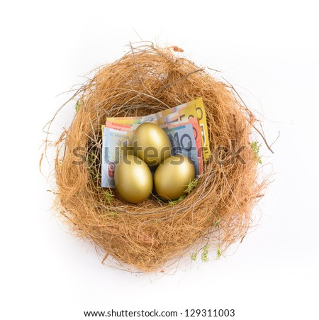 Nest egg with three golden eggs on Australian bank notes - stock photo