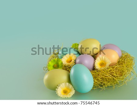 Nest of Brightly Colored Easter Eggs against Blue Background with Copyspace or room or space for your words or text - stock photo