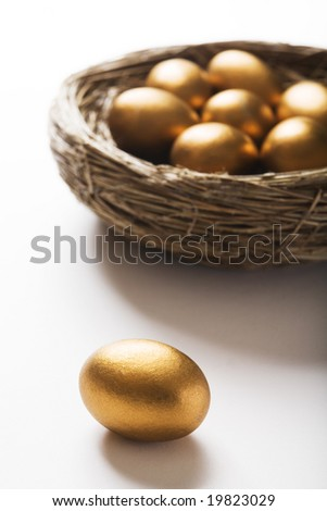Nest Of Golden Eggs With Single Egg In Foreground - stock photo
