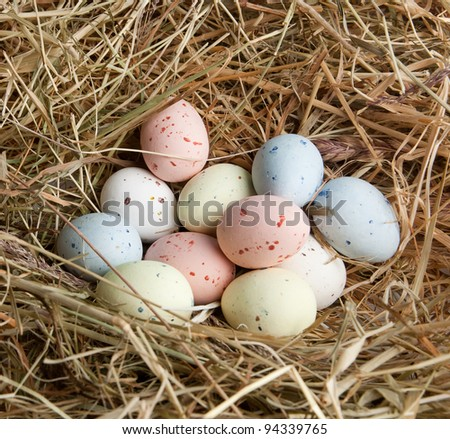 Nest of hay with pastel colored easter eggs - stock photo