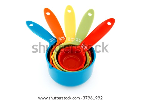Nested colorful measuring cups isolated on white. - stock photo