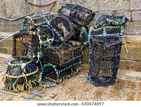 Net and wicker lobster pots;  group of net and wicker traditional creels on fishing quay  - stock photo