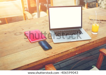 Net-book with mock up copy space screen for advertising text message is lying on wooden table near glass of orange juice, closed notepad and mobile phone. Freelancer supplies on co-working space table - stock photo