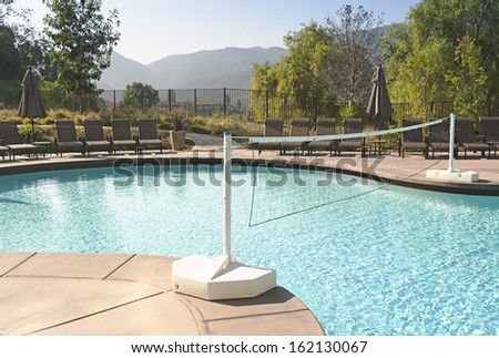 Net for water volleyball across swimming pool - stock photo