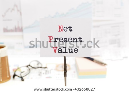 net present value - business concept of  investment  analysis message on the photo holder with background of  stationary, money, compass,  and stock chart  - stock photo