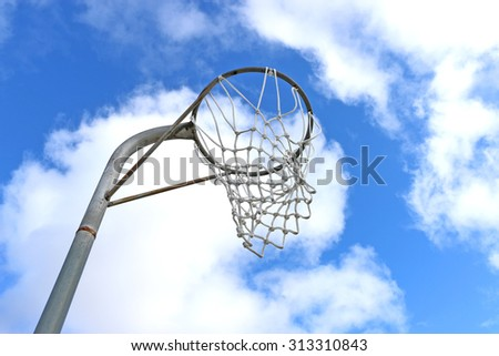Netball goal ring and net against a blue sky and clouds - stock photo
