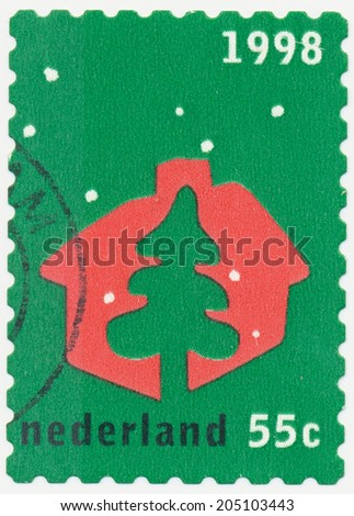 NETHERLANDS - CIRCA 1998: A stamp printed in Netherlands shows Symbolic picture Christmas tree and house, circa 1998 - stock photo