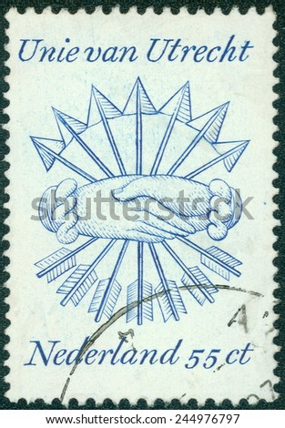 NETHERLANDS - CIRCA 1979: A stamp printed in Netherlands stamp of the Union of Utrecht with shaking hands and arrows, circa 1979 - stock photo