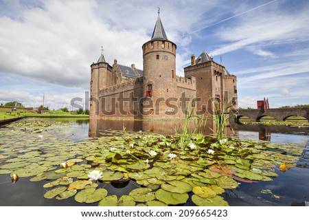 Netherlands, Muiden - June 23 2014: Muiderslot castle with pond and and water lilies on the foreground - stock photo