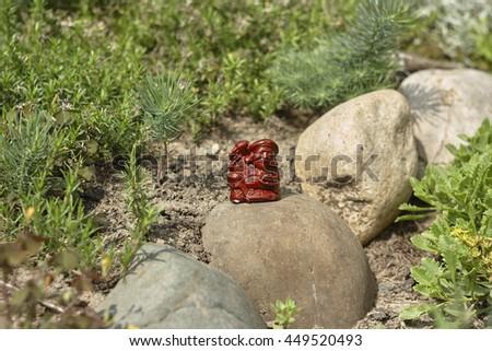 Netsuke worker with hammer on stone in garden - stock photo