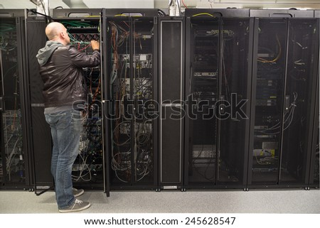Network administrator working on cabling in a server cabinet - stock photo