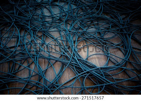 Network chaos of colorful cables on the wooden floor. - stock photo