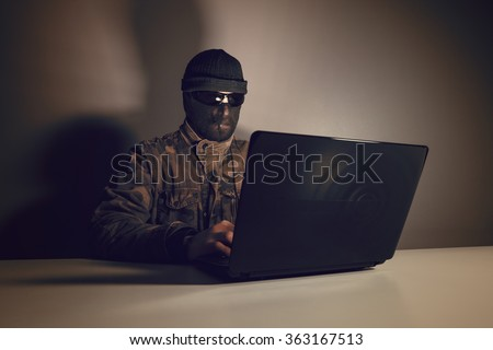 Network criminal man examining a laptop Computer. The man has a camouflage jacket, sunglasses, and balaclava. The photo is underexposed. Image includes a vintage effect.  - stock photo
