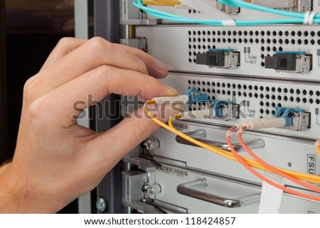 Network engineer insert patch cord - stock photo